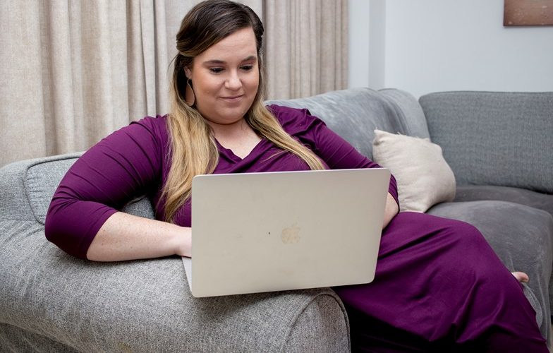 Woman sitting on couch receiving online therapy on laptop