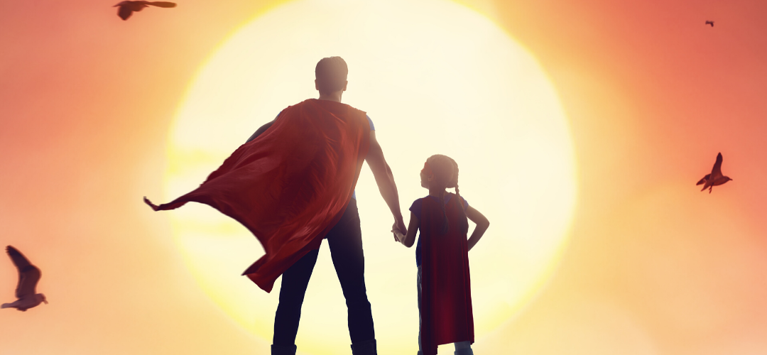 Superhero Dad with daughter standing in front of sunset